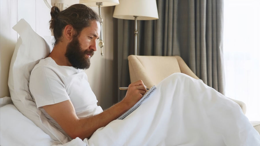 Man holding book while sitting on bed at home