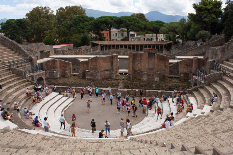 Tourists viewing the large theatre in the ruined city of Pompeii, Italy. Pompeii  Sunny Architecture Building Exterior Built Structure Crowd Day Group Of People High Angle View Large Theatre Leisure Activity Nature Outdoors Real People Sky Sun Theatre Tourism Tourist Travel Travel Destinations Tree