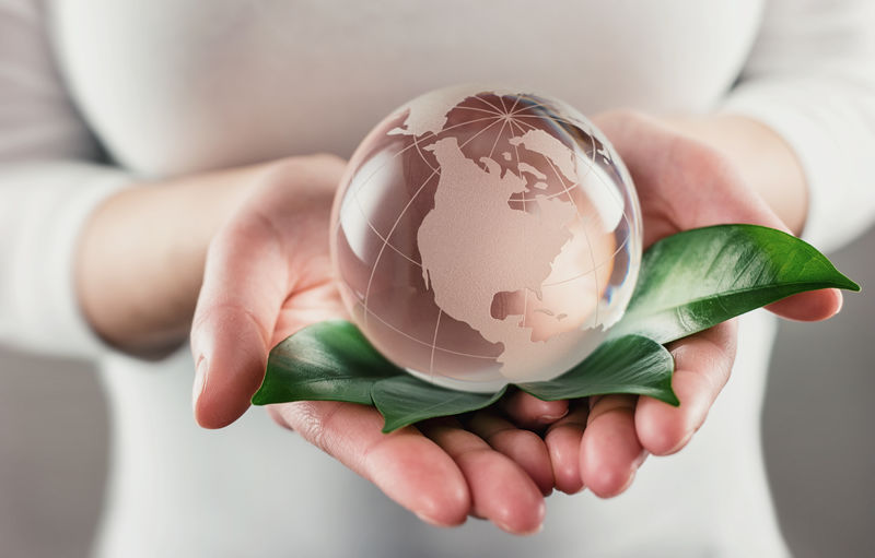 Midsection of woman holding leaves and globe