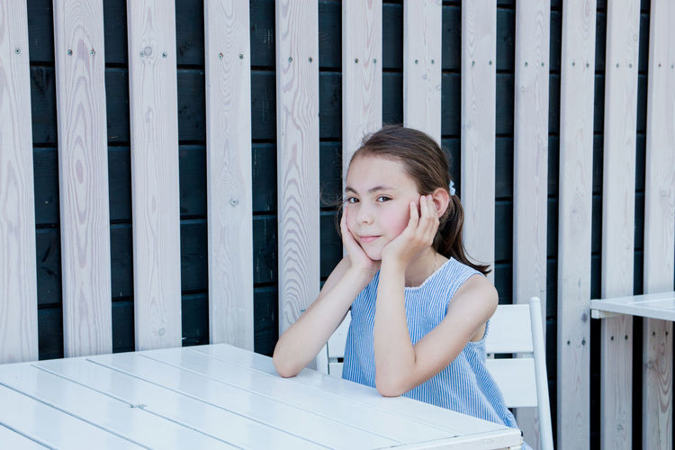 Portrait of smiling girl sitting at table