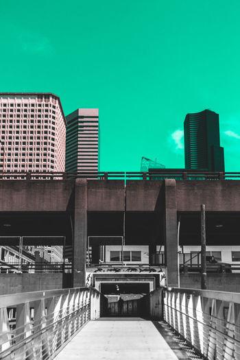Footbridge over city against sky