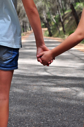 Midsection of child holding hands