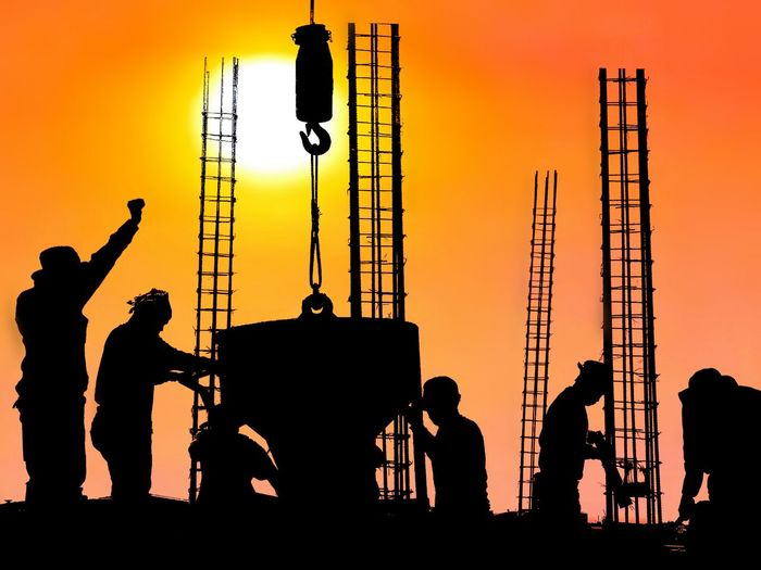 Silhouette construction workers are casting concrete in construction site with blurred sundown sky background on construction and occupation concept Silhouette Blur Background Reinforcement Casting Technology Infrastructure Outdoor Sunset Sundown Morning Evening Bucket Team Project Madon Workplace Colorful Sunset Occupation Manual Worker Silhouette Sky Yellow Background Focus On Shadow Construction Site Construction Worker Construction Crane - Construction Machinery Scaffolding Building Contractor
