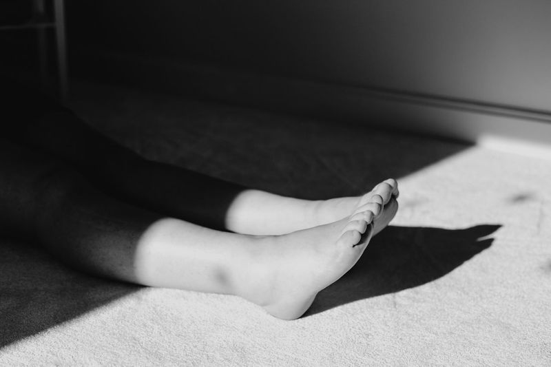 Low section of woman relaxing on floor at home