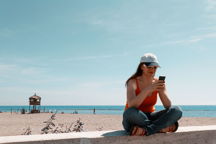 Full length of smiling woman using phone sitting against sea and sky