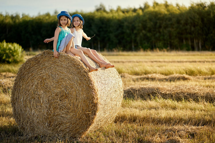 Portrait of woman on hay bales in field
