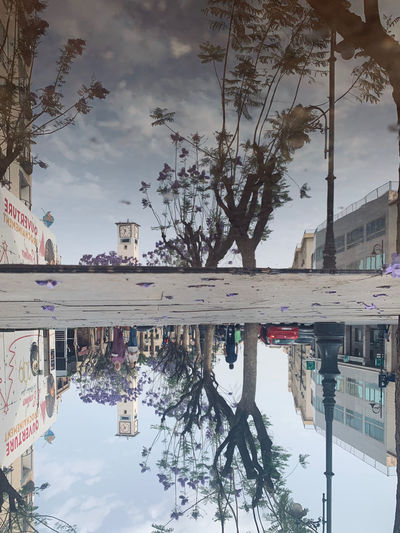 Reflection of building in puddle on city