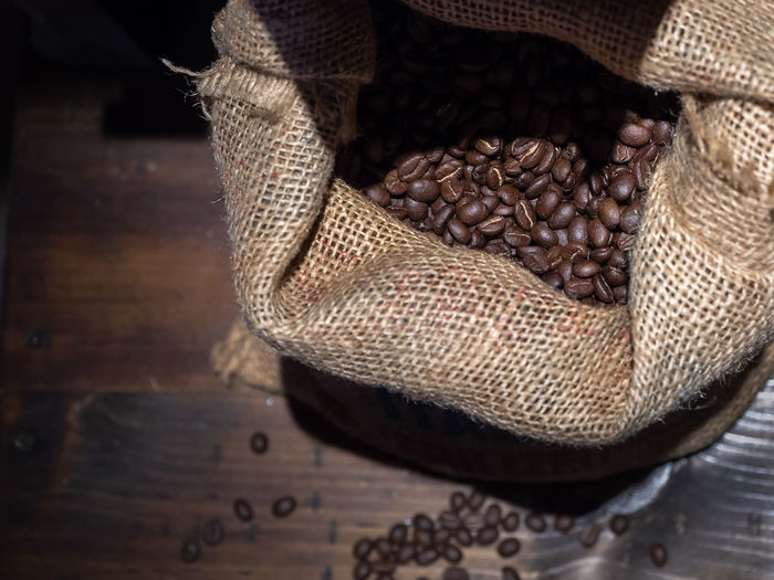 Coffee beans in a bag of sackcloth on wooden background Canvas Coffee Raw Seed Bag Bean Brown Caffeine Close-up Coffee Coffee - Drink Crop  Food Food And Drink Freshness Indoors  Jute No People Object Retro Styled Roasted Coffee Bean Sackcloth Sacks Vintage Wooden