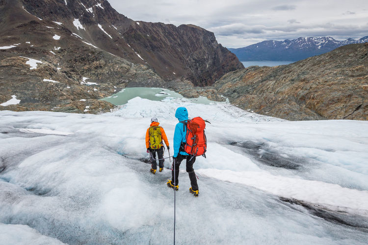 Rear view of hikers moving downhill on glacier
