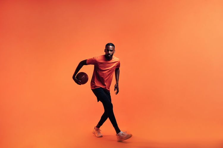 Full length of young man standing against orange background