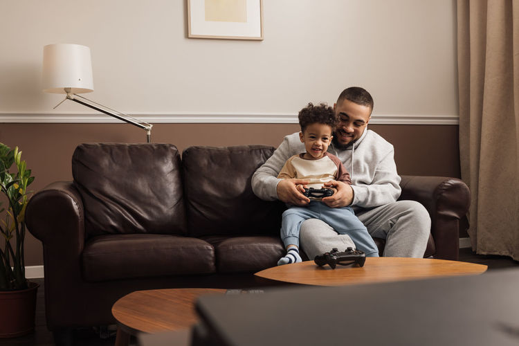 Cheerful father and son playing game at home
