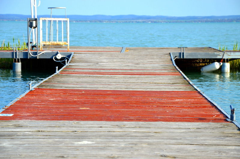 Wooden pier amidst river on sunny day