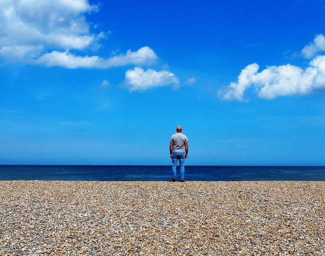 Rear view of man standing at beach against blue sky
