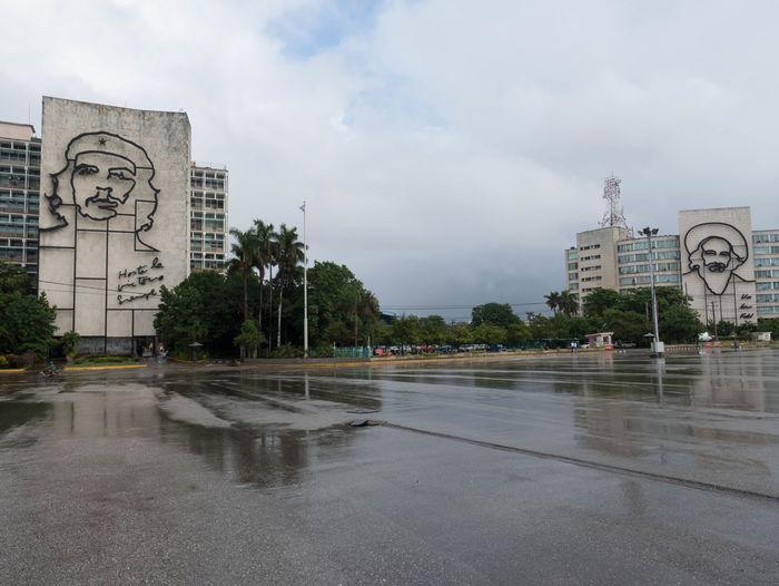 Wet street by buildings in city against sky