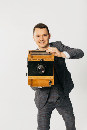 Portrait of young man photographing against white background