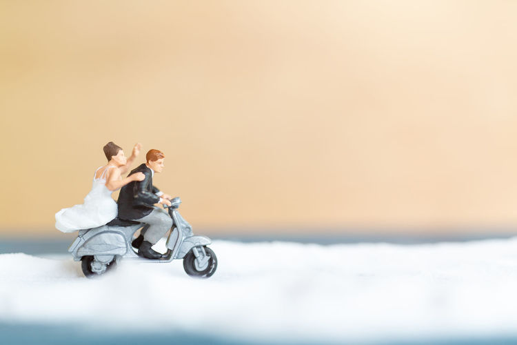 People riding motorcycle on snow against sky