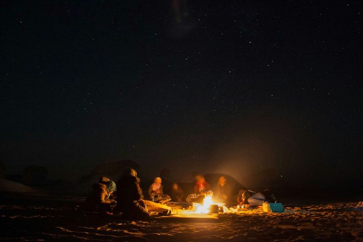 People sitting by bonfire against sky at night