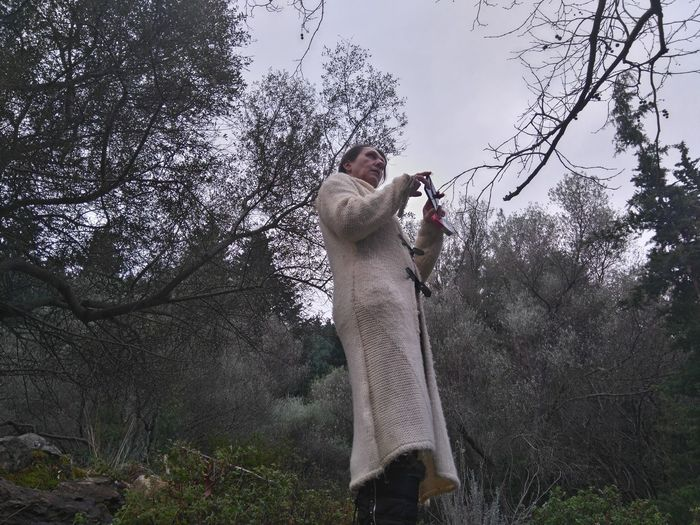 Low angle view of woman photographing on mobile phone while standing against trees