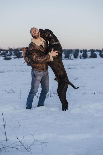 Full length of dog on snow field against sky during winter