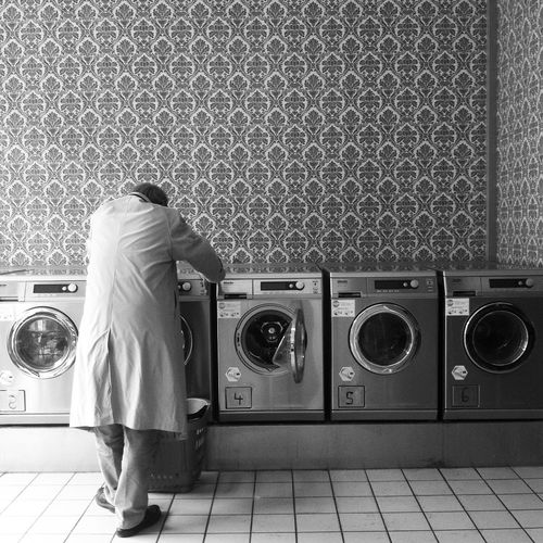 Rear View Of Man Standing By Washing Machines At Laundromat