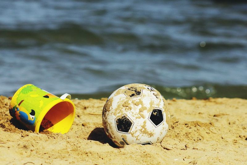 Close-up of soccer ball on beach