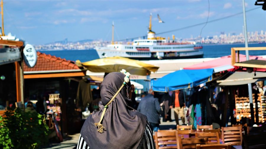 Rear view of woman at market with harbor in background