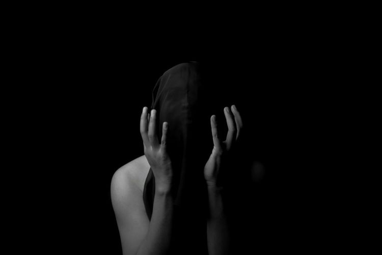 Closeup portait of man covering head in dark background