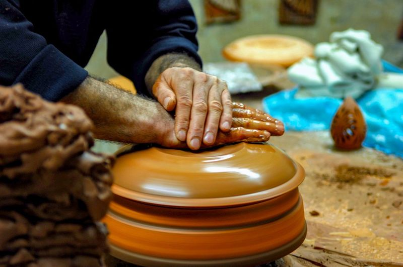 Midsection of potter working at pottery workshop