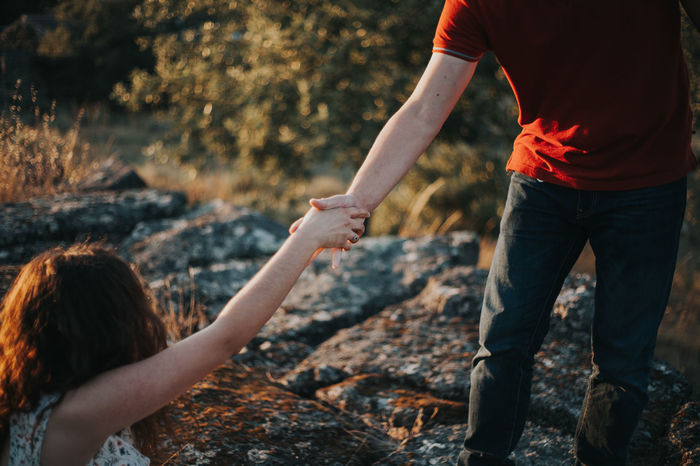 Close-up of couple holding hands in forest