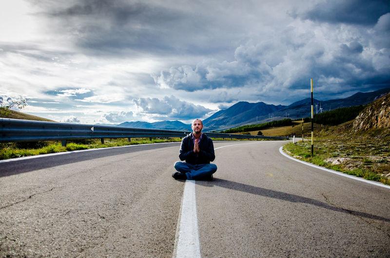 Portrait of man sitting on road against sky