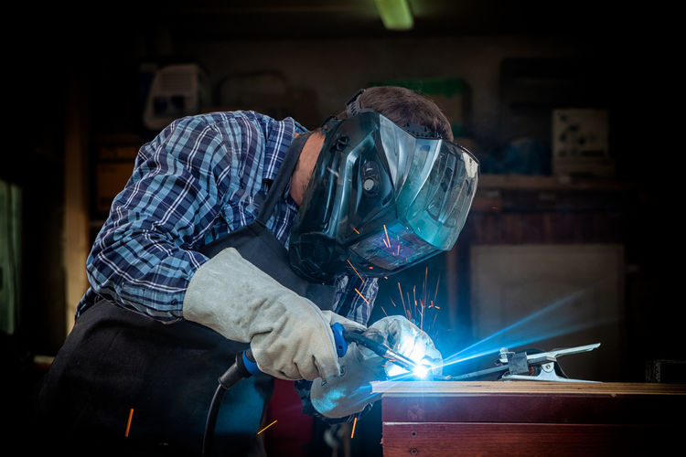 A strong man welder in a black t-shirt, in a welding mask and welders leathers weld metal