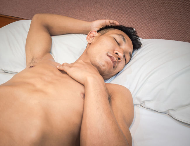 Midsection of shirtless man lying on bed