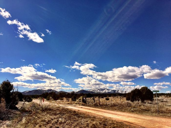 """Cattle Cross To Nirvana"" Spectacular clouds, snow covered mountains and an enticing dirt country road seemingly bekon to those who cross the cattle guard. Country Road Rural Scenes Rural America Rural Landscape RuralTreasures  Cattleguard Snowcoveredmountains Clouds And Sky"