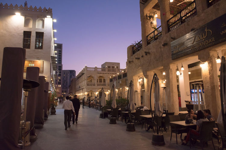 Souq Waqif Doha Adult Architecture Building Building Exterior Built Structure City Dusk Group Of People Illuminated Incidental People Lighting Equipment Men Nature Night Outdoors People Qatar Real People Sky Souk Street Travel Destinations Waqif Women