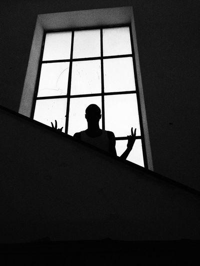 Silhouette man gesturing victory sign against window