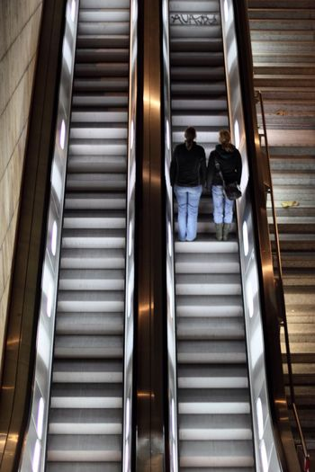 Rear view of two women moving up on escalator