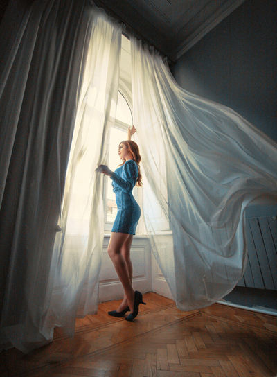 Low angle view of woman standing by window at home