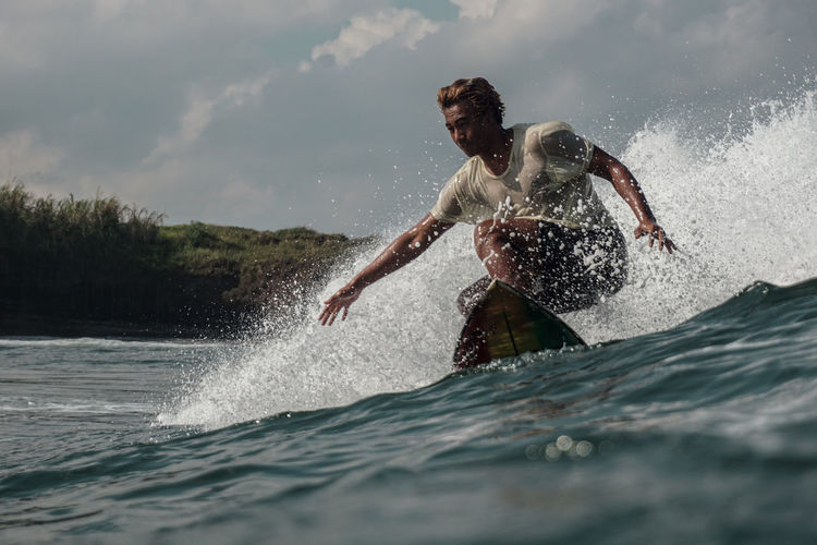 Man splashing water while surfing in sea against sky