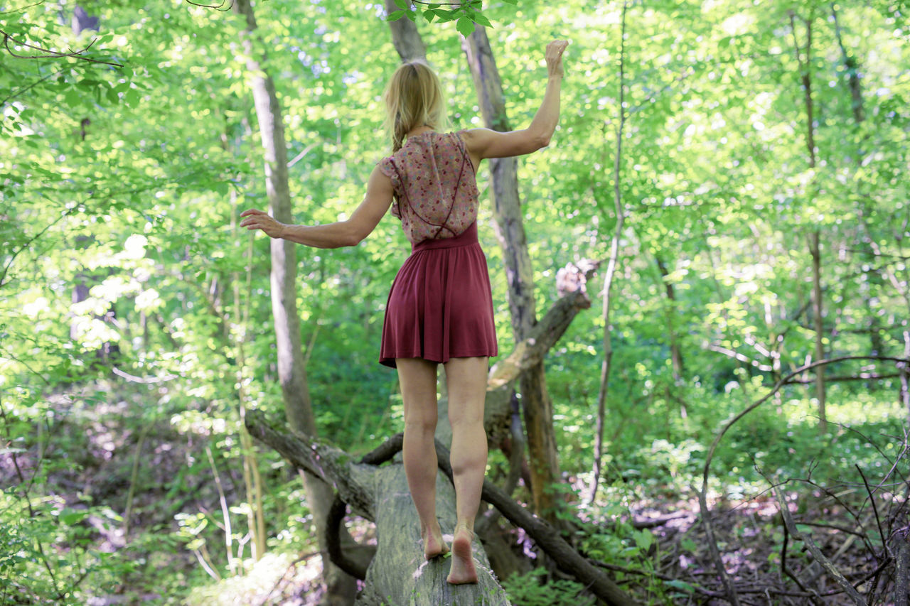 Rear View Of Young Woman Walking On Fallen Tree Trunk At Forest