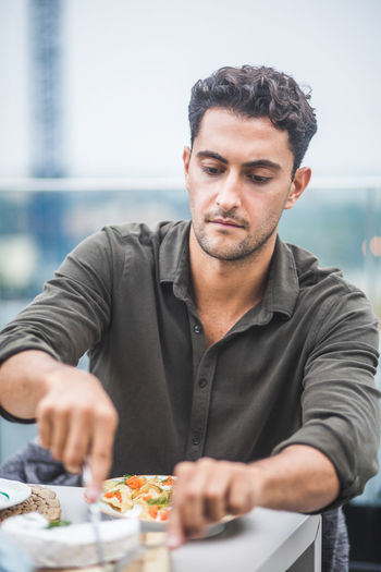 Midsection of man having food in restaurant