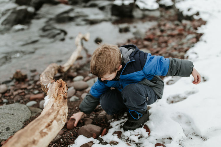 Boy playing with rock on lakeshore during winter