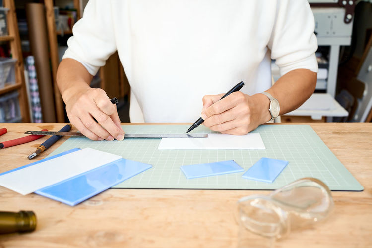 Midsection of man measuring tiles at table