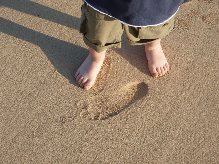 Beach Childhood Childs Footprint On Sand Foot Prints In The Sand Human Body Part Human Foot Human Leg Innocence It Wasent Me Lifestyles Part Of Person Personal Perspective Real People Relaxation Standing