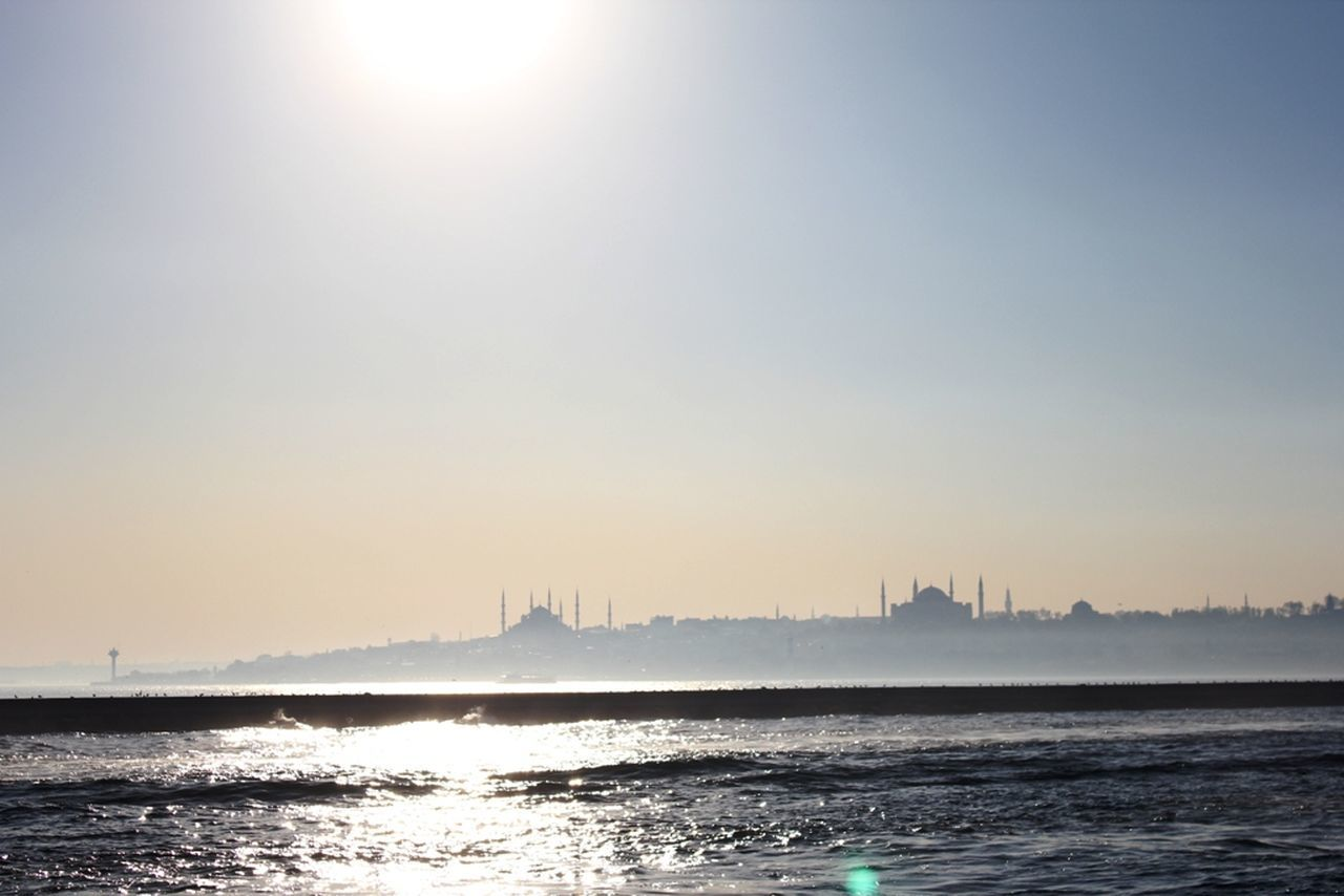 water, sunlight, sun, built structure, waterfront, sky, architecture, no people, sea, outdoors, sunset, building exterior, skyscraper, city, day, nature, clear sky, beauty in nature, cityscape
