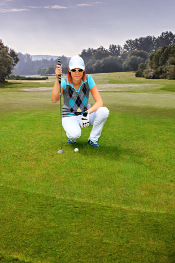 female golf player with a golf club on the course Action, Activity, Bag, Ball, Clubs, Course, Driver, Females, Field, Fun, Girl, Golfer, Golfs, Grass, Greens, Hobby, Iron, Outdoors, People, Play, Playing, Putting, Sports, Summer, Swing, Tee, Vacations, Woman, Women, Young Activity Casual Clothing Day Field Front View Full Length Golf Grass Green Color Leisure Activity Looking At Camera Nature One Person Outdoors Plant Portrait Real People Sport Young Adult