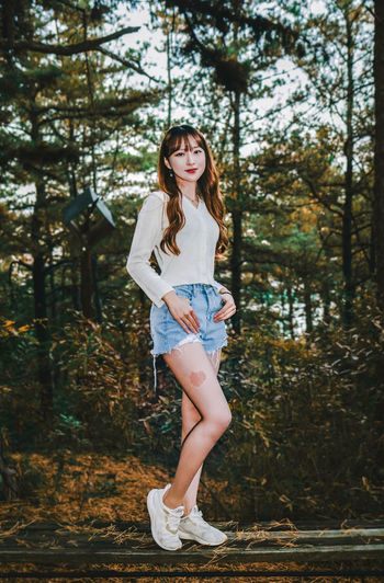 Portrait of young woman standing against trees in forest