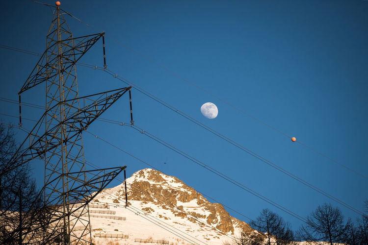 balls in the sky Moon Sky Powerline Balls Mountain Snowcapped Mountain Winter Evening Outdoors Built Structure Trees Clear Sky Blue Cable Technology Cold Temperature Electricity  Connection 17.62°