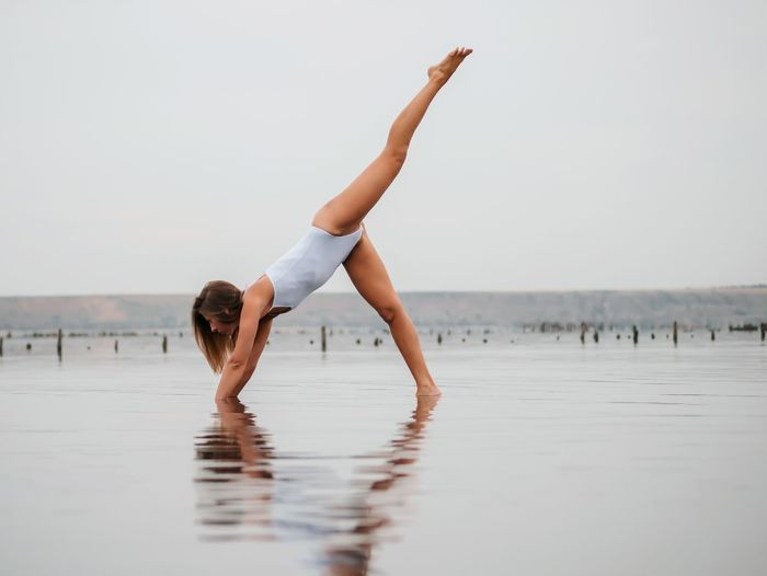 Water Exercising Leisure Activity Young Adult Yoga Full Length Sea Young Women Balance Beach Lifestyles Flexibility Day Barefoot One Person Tranquil Scene Stretching Nature Tranquility Beautiful Woman