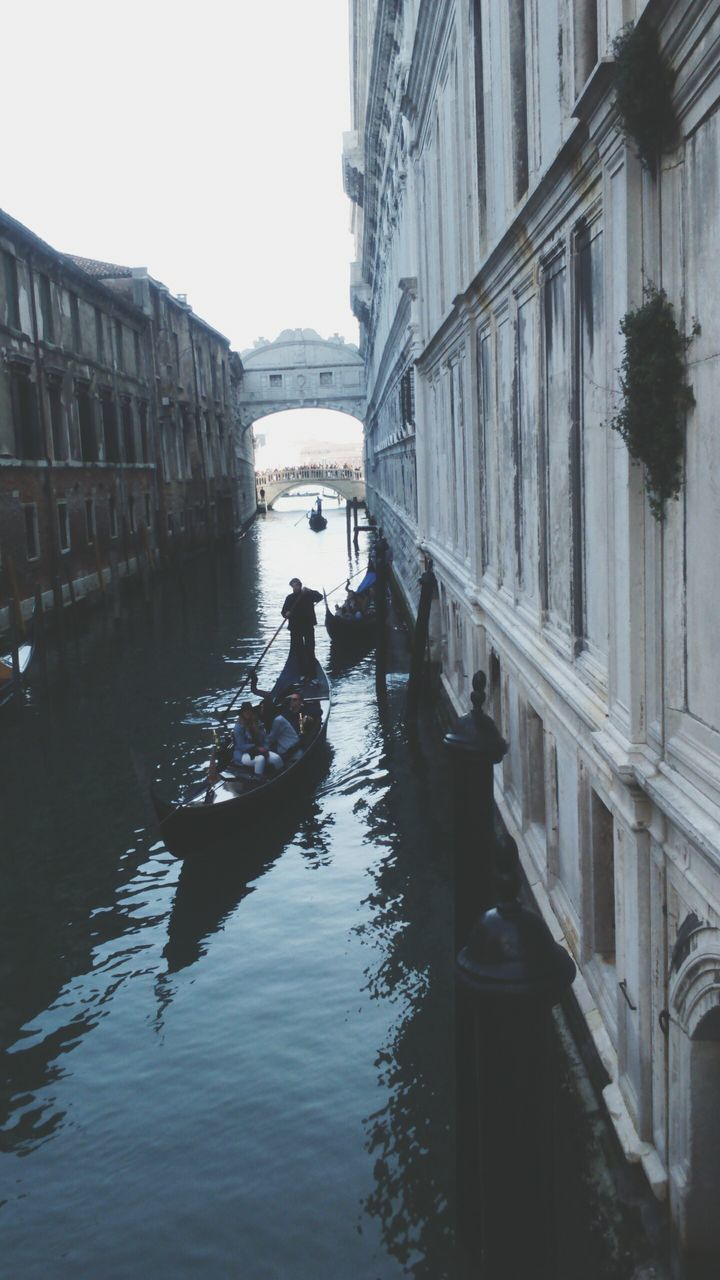 architecture, gondola - traditional boat, gondolier, canal, transportation, building exterior, real people, day, built structure, nautical vessel, men, outdoors, oar, gondola, rowing, one person, water, full length, occupation, city, people