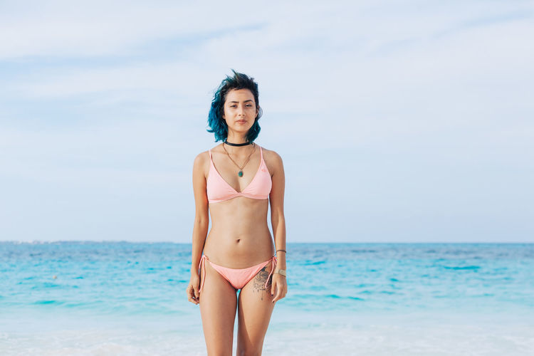 Portrait Of Woman In Bikini Standing At Beach Against Sky
